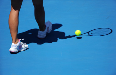 A female tennis players legs are shown with a shadow