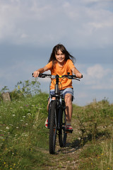 Girl riding bike in rural scenery