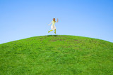 woman jumping on a green meadow