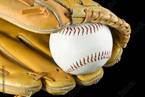 Basball and baseball glove isolated on black.
