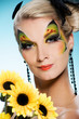Young beauty with butterfly face-art and bouquet of sunflowers