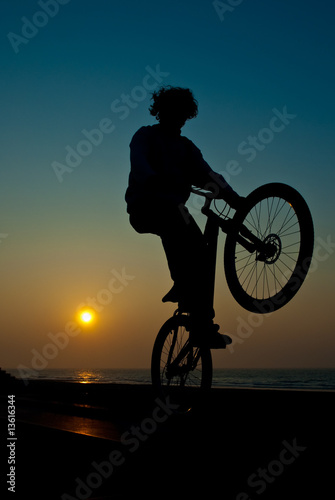young man performing bike tricks