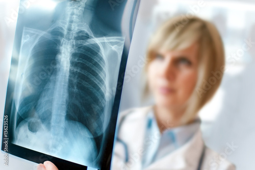 Female doctor examining an x-ray - 13623526