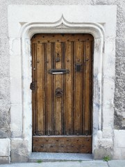 Old wooden door with medieval carved stone lintel
