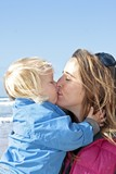 Mom and little blonde boy cuddling and kissing poster