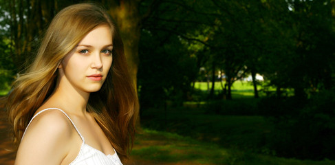 Cute young Teen Girl in a German park with dark background