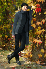 Fashion portrait of young woman posing in a park in autumn