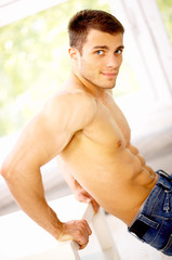 Muscular and tanned male is exercising, wearing jeans