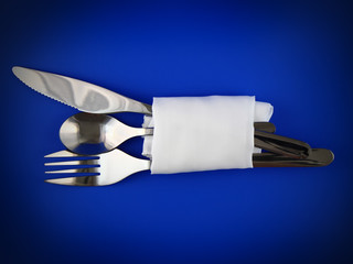 Knife fork and spoon, bound by napkin on blue background.