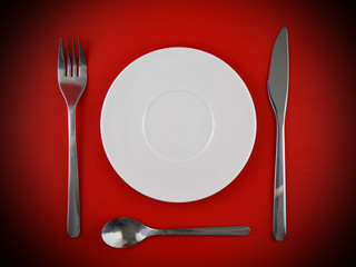 Fork, knife, spoon, plate on red  background
