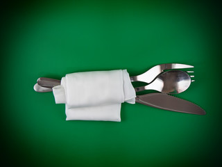 Knife fork and spoon, bound by napkin on  green background.