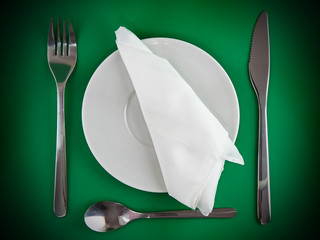 Fork, knife, spoon, plate, and silk napkin on green  background