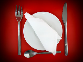 Fork, knife, spoon, plate, and silk napkin on red  background