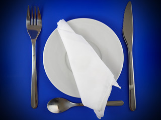 Fork, knife, spoon, plate, and silk napkin on blue background