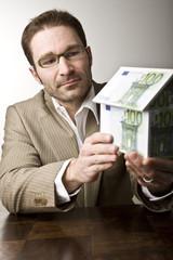 Junger Mann mit Haus aus Geldscheinen