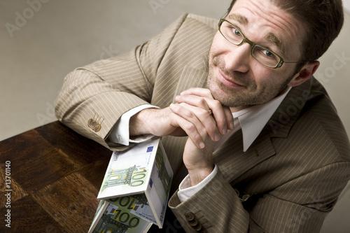 Leinwanddruck Bild Junger Mann mit Haus aus Geldscheinen