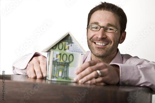 Leinwanddruck Bild Junges Paar mit Haus aus Geldscheinen
