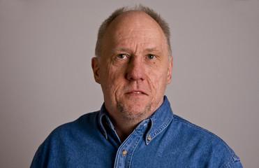 Older Bald Guy in Blue Denim Shirt Looking Over Camera