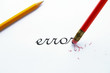 "pencil erasing an ""error"" on white paper"