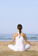 Frau im Lotussitz meditiert am Strand