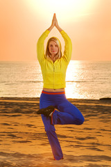 Beautiful young woman doing fitness exercise on a beach at sunse