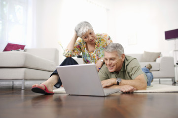 Senior couple at home looking at laptop computer