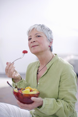 Senior woman eating bowl of fruit