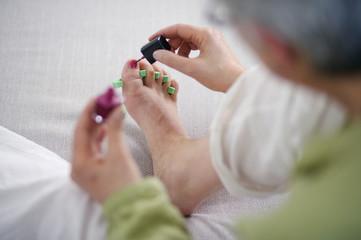 Senior woman giving herself at pedicure at home