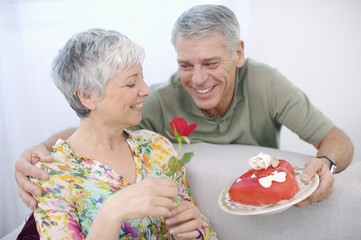 Senior man romancing woman with valentine cake and red rose