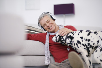 Happy senior man listening to music on headphones with Dalmatian at home