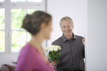 Mature man holding white roses for woman