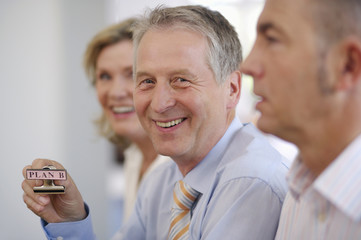 Portrait of mature man holding Plan B pin, selective focus