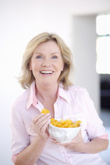 Portrait of mature woman with bowl of potato chips