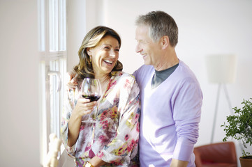 Happy mature couple at home drinking wine