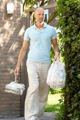 Mature man carrying garbage bags, Den Haag, Netherlands