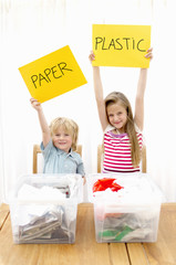 Boy and girl holding paper and plastic sign with recycling containers in foreground, Den Haag, Netherlands