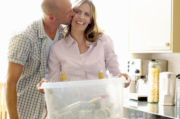 Mature woman holding recycling container of glass bottles with man kissing her cheek