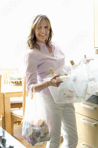 Mature woman holding recycling container of glass bottles