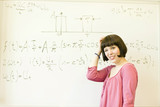 Portrait of confused young woman standing before an equation on the board