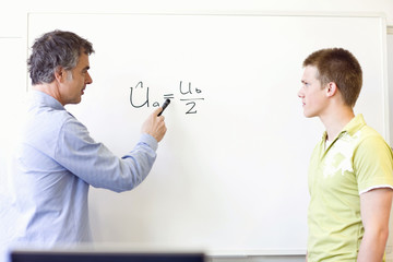Teacher and student at board discussing an equation