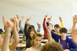 Students in classroom sitting at desks raising hands