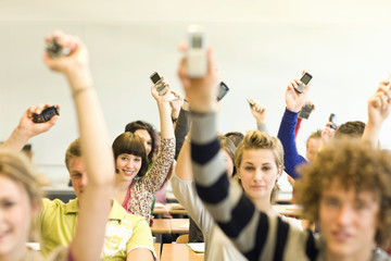 Students in classroom sitting at desks raising cell phones in the air