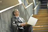 Businessman sitting on staircase with eyes closed holding laptop