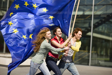 Three young people smiling and walking with an EU flag in Munich, Bavaria, Germany