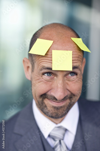 Portrait of mature man with three note papers stuck on forehead