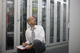 Mature man checking computers in server room
