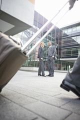 Low angle view of two businesspeople standing in front of office building Munich, Bavaria, Germany