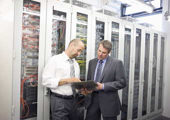 Two mature man checking computers in server room