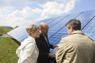 Three mature adults reading plans laid on solar panels in Munich, Bavaria, Germany
