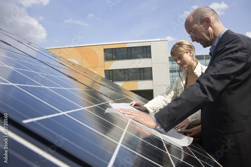 Two mature adults reading plans laid on solar panels in Munich, Bavaria, Germany